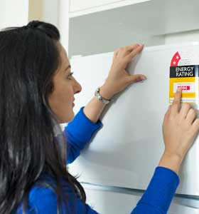 A woman looks at the Energy Ratings logo on her fridge.